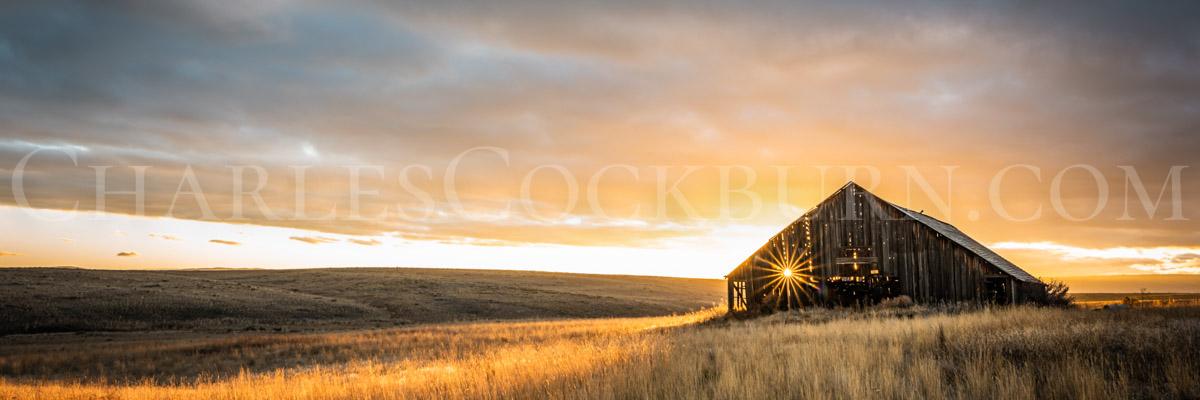 The setting sun sparkles through the crumbling wood of an ancient barn on the prairie near Douglas, Washington | CharlesCockburn.com